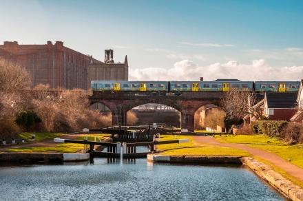 Merseyrail train in new livery at Stanley Dock on canal bridge.