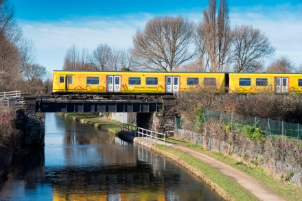 Merseyrail Electrics train at Old Roan crossing the Leeds Liverpool canal.
